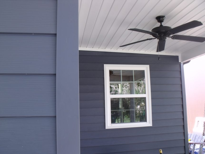 A beautiful deep blue steel siding job showing completed corners with windows trimed in white