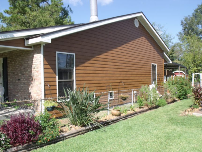Side view of home installed with carmel colored steel siding with white trim
