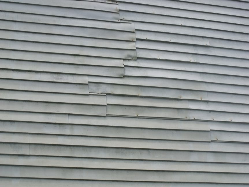 Home owner has repaired vinyl siding with hammer and nails